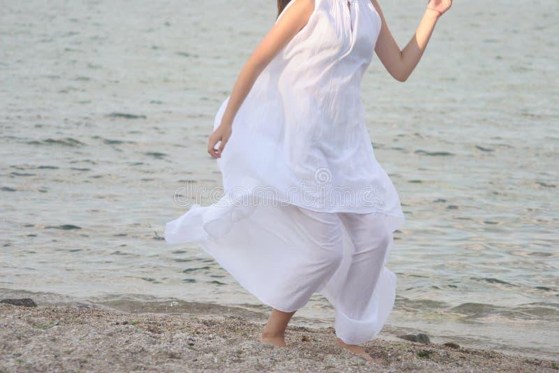 Frau im weißen Kleid läuft entlang den sandigen Strand lizenzfreie stockfotos