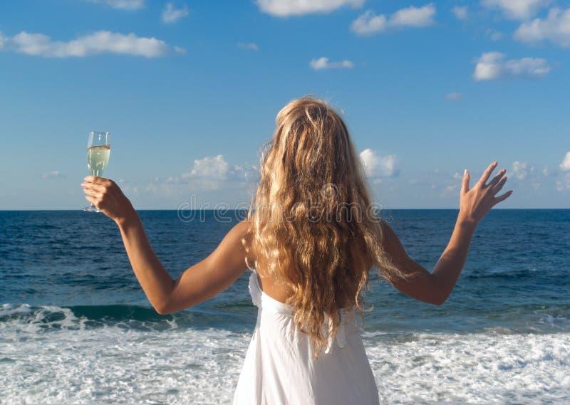 Frau im weißen Kleid nahe dem Meer, das weit schaut stockfotografie