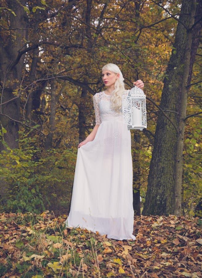 Frau im weißen Kleid und in einer Laterne stockfotografie