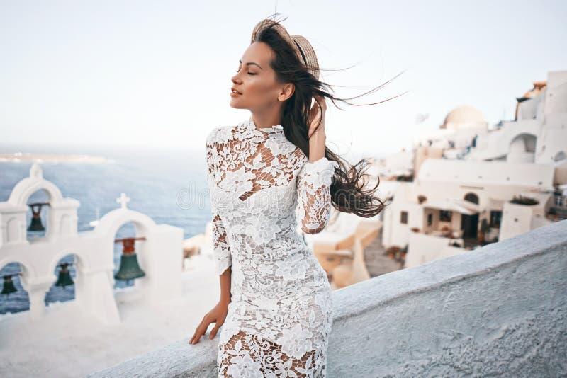 Frau im weißen Kleid und im Strohhut auf Santorini-Insel lizenzfreie stockfotos