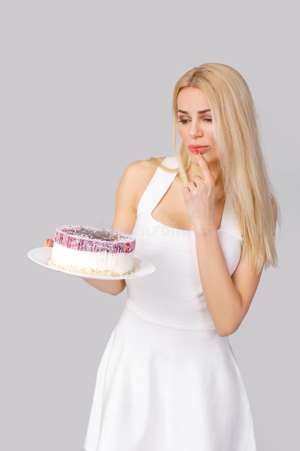 Frau im weißen Kleiderholdingkuchen stockfoto