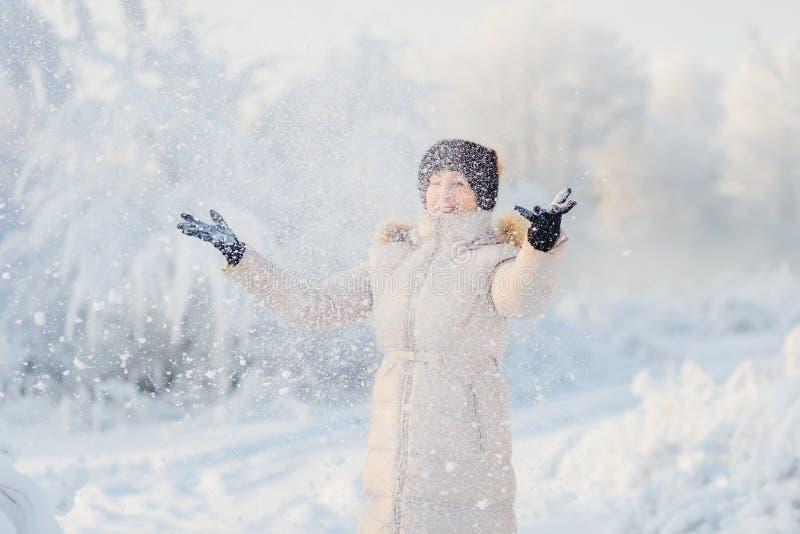 Frau im weißen Mantel, Wurfsschnee lizenzfreie stockfotografie