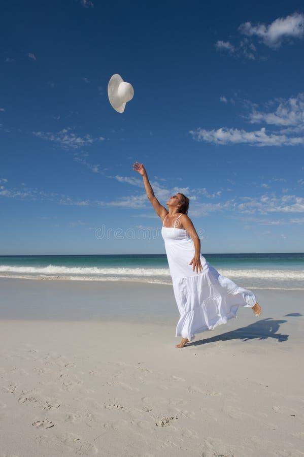 Frau im weißen Sommer-Kleid auf Strand stockfoto