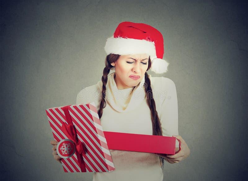 Frau im Weihnachtsmann-Hutöffnungs-Geschenkumkippen stockfoto