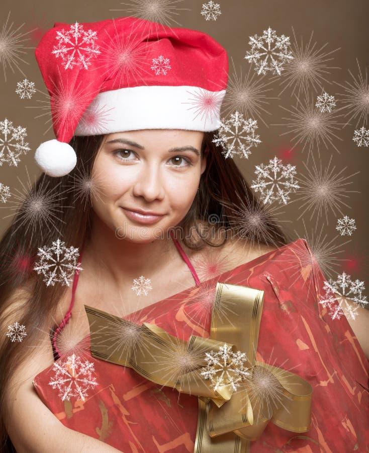 Frau im Weihnachtsmann-Hut mit Geschenk in den Händen lizenzfreies stockbild