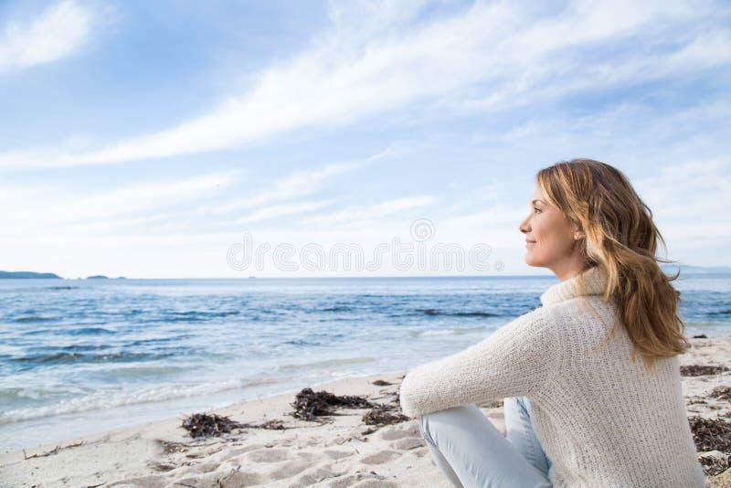 Frau im Winter auf dem Strand lizenzfreies stockbild
