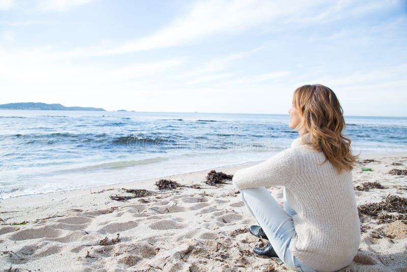 Frau im Winter, der auf dem Strand sitzt stockbild