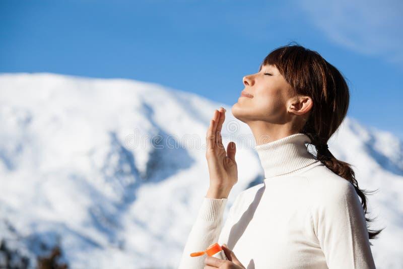 Frau im Winter schützende Creme auftragend lizenzfreies stockfoto