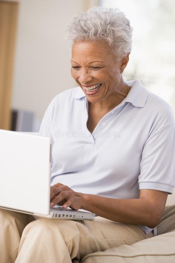 Frau im Wohnzimmer mit dem Laptoplächeln lizenzfreie stockfotografie