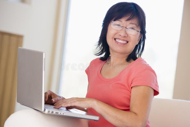 Frau im Wohnzimmer mit dem Laptoplächeln stockfotos