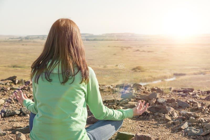 Frau im Yoga und meditiert im Lotussitz stockfotografie