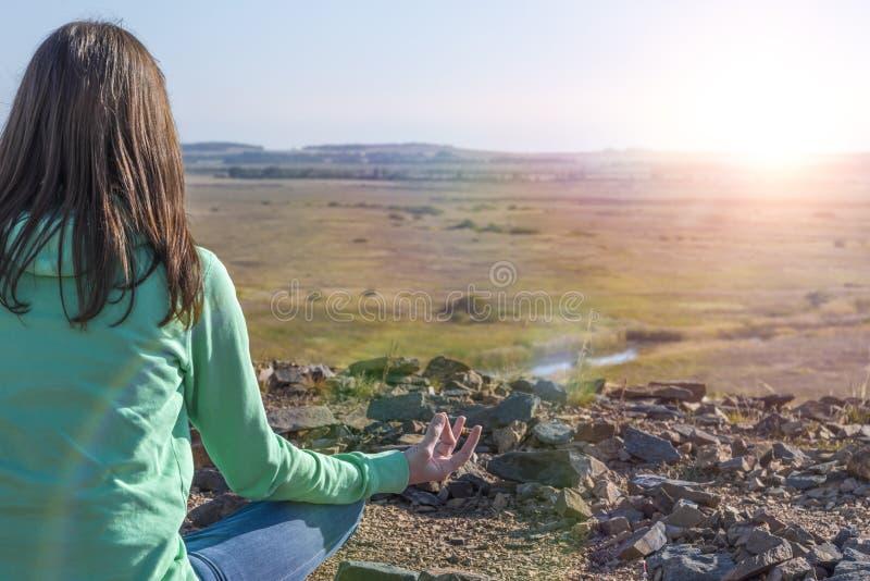 Frau im Yoga und meditiert im Lotussitz auf einem Berg stockbild