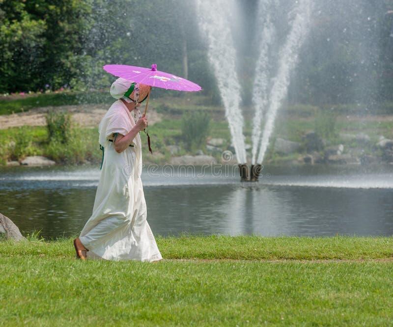 Frau im Zeitraum-Kostüm durch Brunnen lizenzfreie stockfotos
