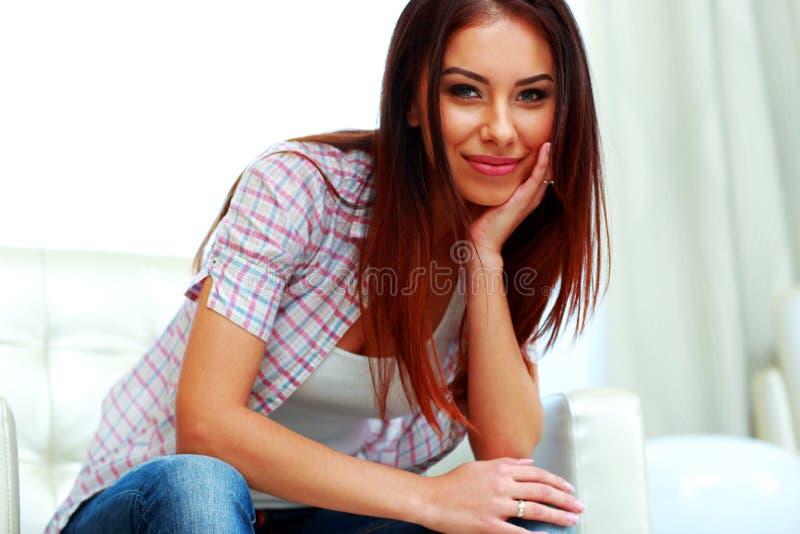 Frau im zufälligen Stoff, der auf dem Sofa sitzt stockfoto