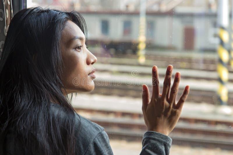 Frau im Zug, die heraus das Fenster schaut stockfoto