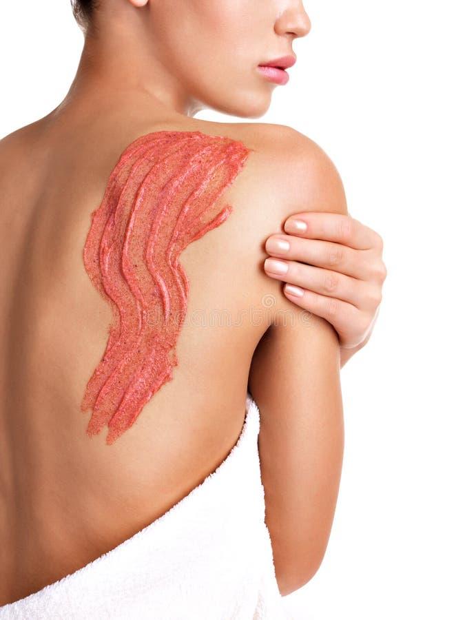 Frau interessiert sich für die Haut des Körpers Kosmetik verwendend sich scheuern auf der Rückseite stockfotos