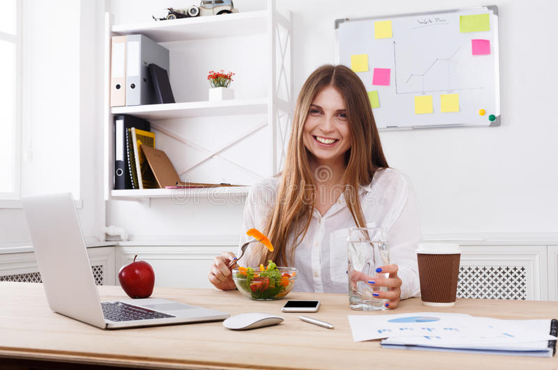 Frau isst gesunden Business-Lunch im modernen Büroinnenraum zu Mittag lizenzfreie stockfotos