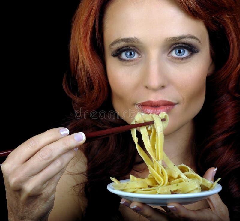 Frau isst Teigwaren stockfotos