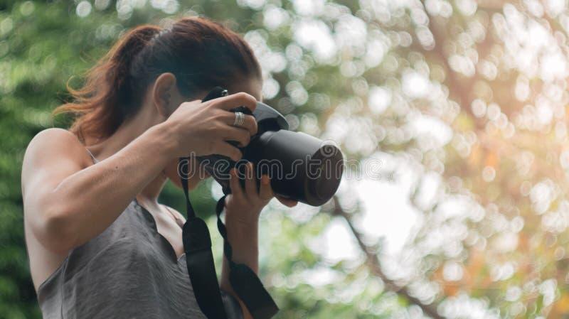 Frau ist ein Berufsfotograf mit dslr Kamera, Weichzeichnung, natürliches bokeh lizenzfreie stockfotografie