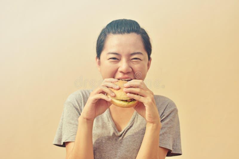Frau ist, genießend essend und einen Hamburger lizenzfreie stockfotografie