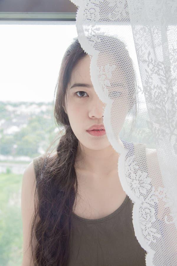 Frau ist hinter dem Vorhang stockbild