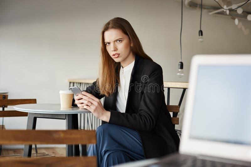 Frau ist insulter mit den offensiven Wörtern des Fremden sitzend mit Laptop Porträt der gestörten attraktiven Frau im Café lizenzfreies stockbild