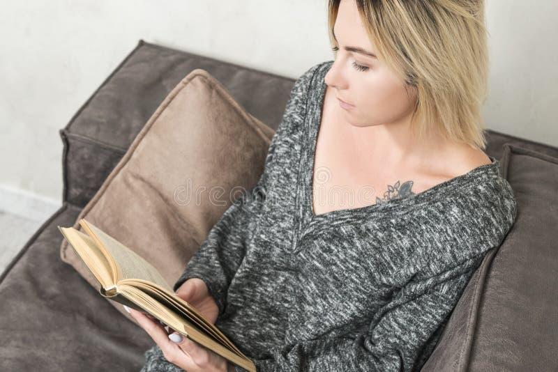 Frau ist Lesebuch auf dem Sofa stockfoto