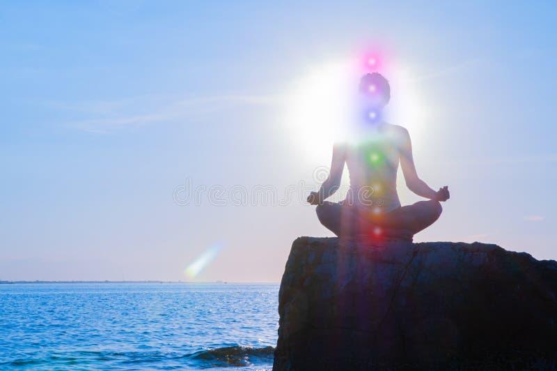 Frau ist meditierendes mit Glühen sieben chakras auf Stein bei Sonnenuntergang Schattenbild der Frau übt Yoga auf dem Strand lizenzfreies stockbild