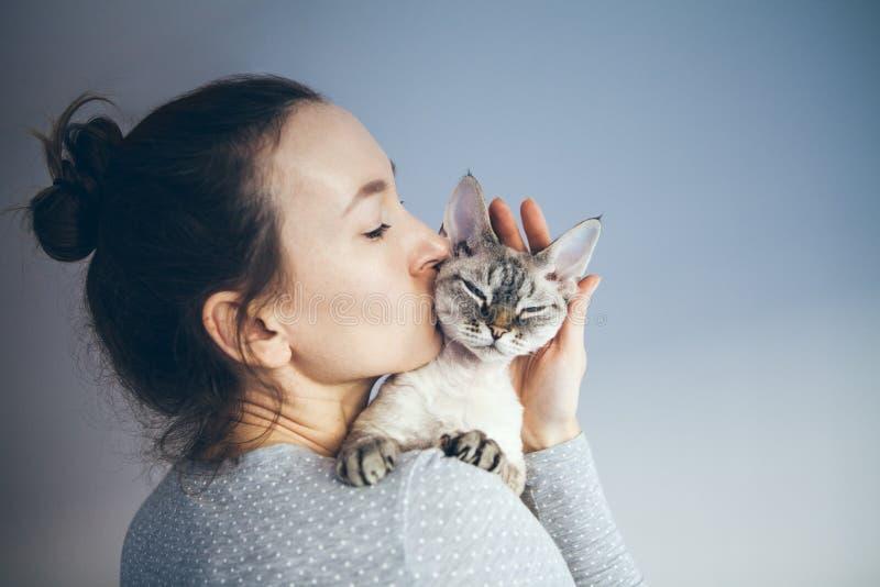 Frau ist, streichelnd küssend und ihre süße und nette schauende Devon Rex-Katze Kätzchen fühlt sich glücklich, mit seinem Inhaber stockfotografie
