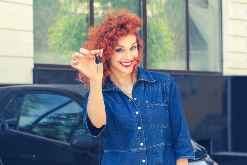 Frau, Käufer nahe ihrem Neuwagen, der Schlüssel gebend darstellt lizenzfreie stockfotografie