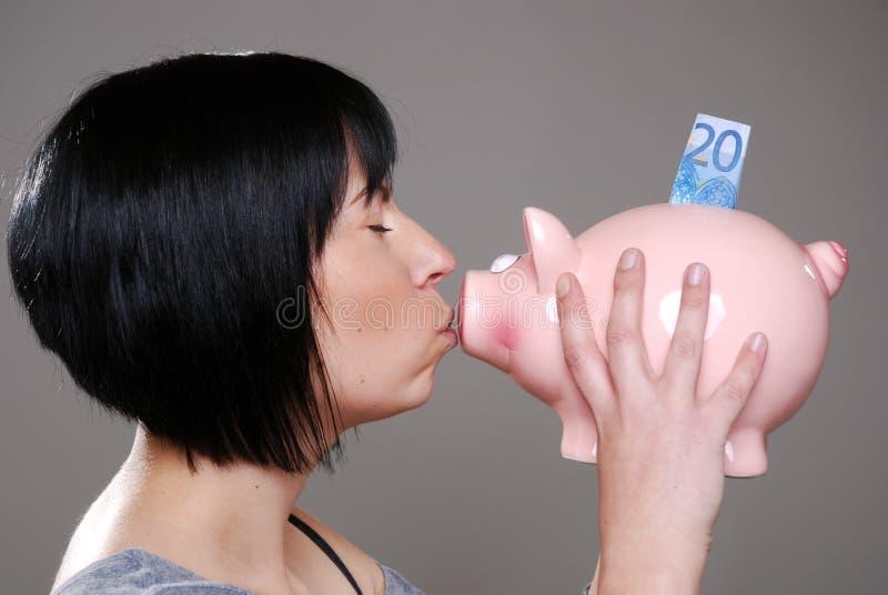 Frau küßt piggybank lizenzfreie stockbilder