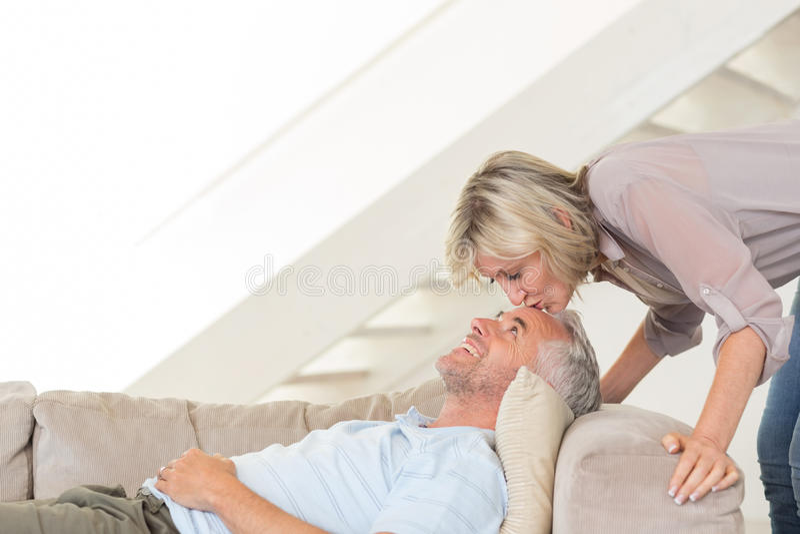 Frau küssendes a bemannt Stirn im Wohnzimmer stockbilder