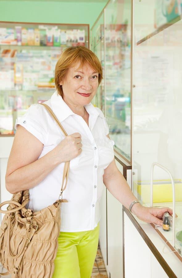 Frau kauft Drogen an der Apotheke stockbilder