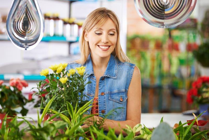 Frau kauft im Blumenladen lizenzfreies stockfoto