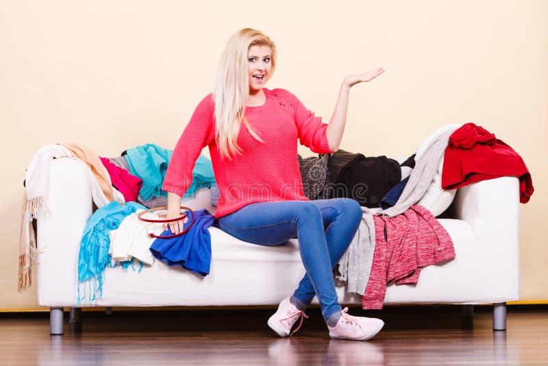 Frau kennt nicht was, das Sitzen auf Couch zu tragen lizenzfreies stockbild