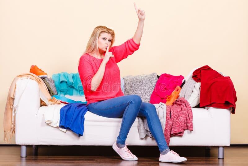 Frau kennt nicht was, das Sitzen auf Couch zu tragen lizenzfreie stockbilder