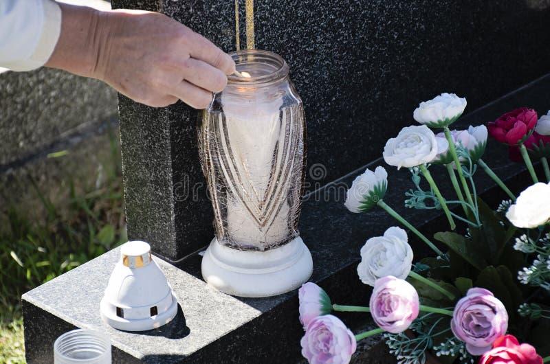 Frau am Kirchhof beleuchtet eine Kerze mit einem Match auf dem Grab stockbild