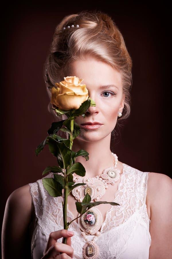 Frau kleidet in der Victorianart an, die ihr Auge mit einer Rose bedeckt stockfoto