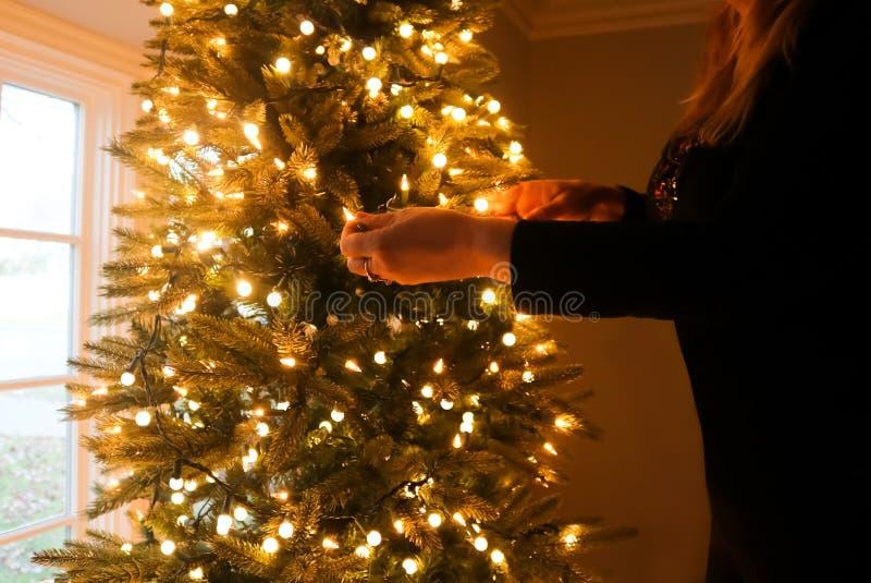 Frau kleidete im schwarzen Verzierungsweihnachtsbaum mit Lichtern an lizenzfreie stockfotos