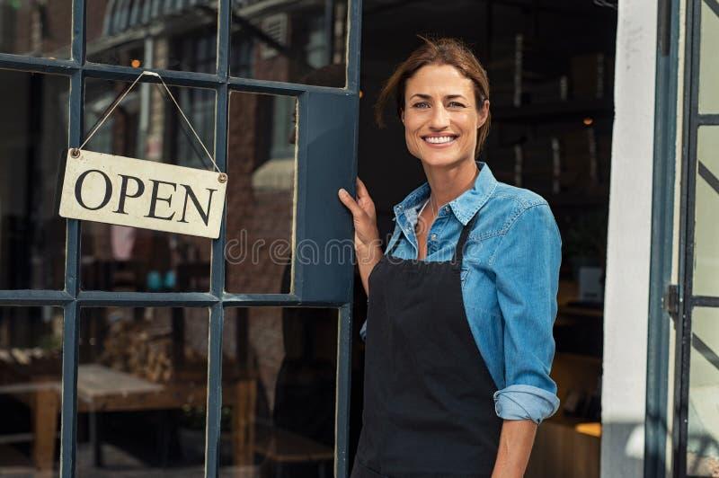 Frau am Kleinbetriebeingang stockfoto
