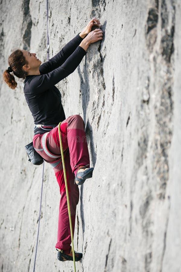 Frau klettert einen Felsen lizenzfreie stockfotos