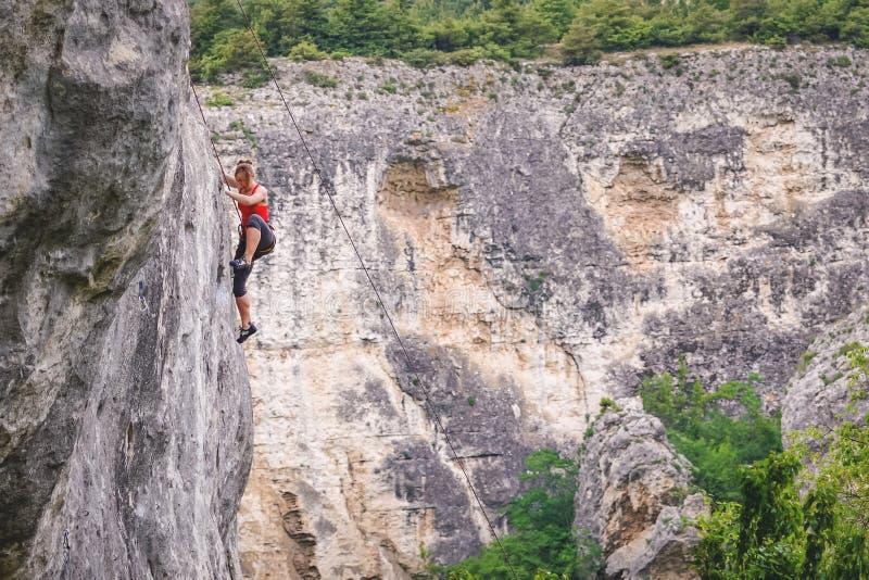 Frau klettert Felsen stockfotografie