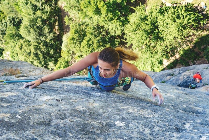 Frau klettert Felsen stockfotos