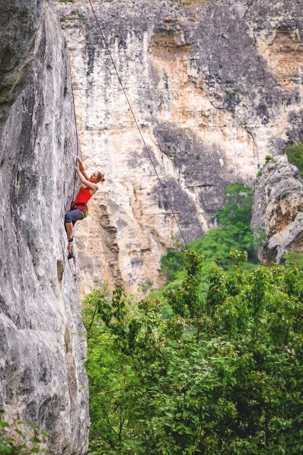 Frau klettert Felsen stockbild