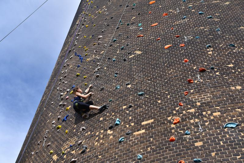 Frau klettert oben eine künstliche Felsenwand -, die mit Seil AG gesichert wird lizenzfreie stockfotos