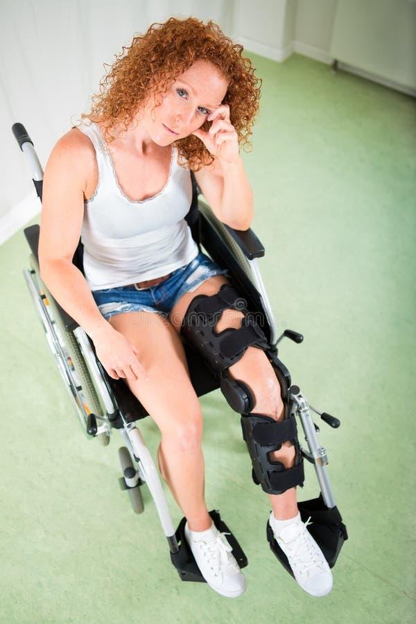 Frau kurz gesagt und T-Shirt gesetzt im Rollstuhl lizenzfreie stockfotografie