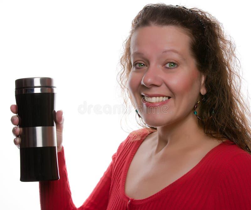 Frau lächelt und hält eine Flasche Flüssigkeit an. stockfotografie