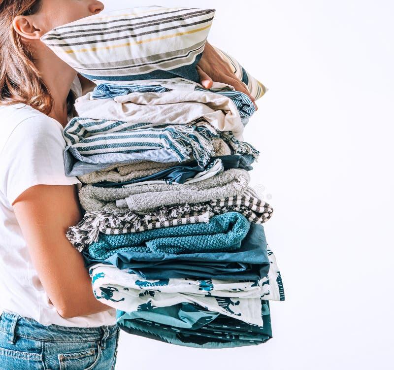 Frau lässt blaue und beige Decken des Handgroße Stapels, Tücher und anderes Hauptgewebe ein stockbild