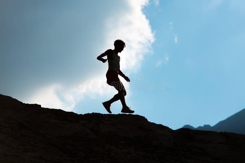 Frau läuft abwärts auf Gebirgspfad lizenzfreie stockfotos