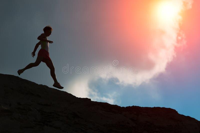 Frau läuft auf der Kante mit bunter Sonne lizenzfreie stockfotografie